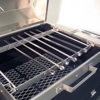 The custom skewer rack replaces the cooking grate